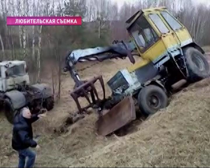 Из придорожного кювета пытаются вытащить трактор